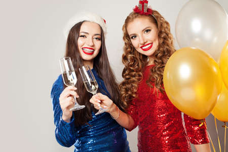 Happy Christmas women chin-chin. Smiling girls with sparkling wine glasses Фото со стока