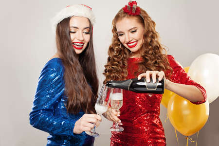 Two happy women with sparkling wine bottle, Merry Christmas or Happy New Year party portrait Фото со стока
