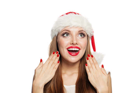 Surprised Christmas woman in Santa hat and red manicured nails isolated on white background. Фото со стока