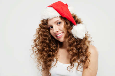 Happy young woman in Santa hat smiling on white background.