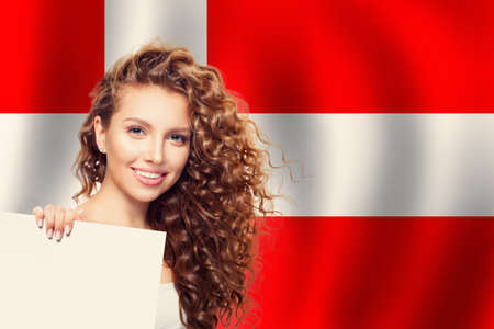 Travel and learn danish language concept. Smiling woman student showing white paper Denmark flag background 版權商用圖片