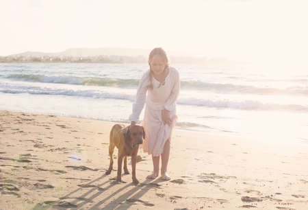 Blonde girl in white dress with a dog playing in the morning on the beach Stock fotó