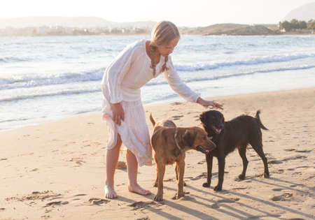 Blonde girl with a dogs playing in the morning on the beach Stock fotó - 135466036