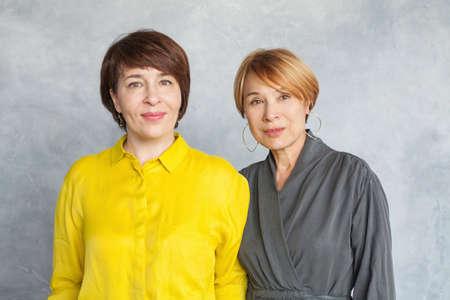Elegant mature women portrait. Two ladies with short haircut
