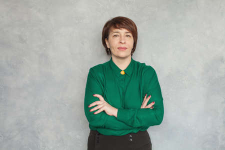 Portrait of middle aged business woman on gray