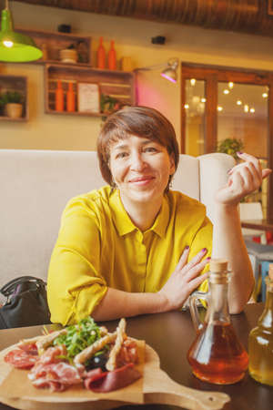 Happy middle aged woman in cafe, portrait