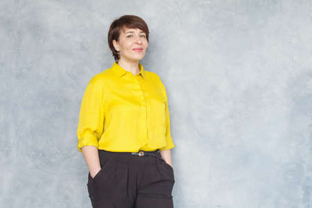 Mature business woman in yellow shirt smiling, portrait