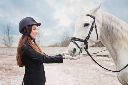 Glückliche Jockeyfrau, die draußen weißes Pferd füttert Standard-Bild