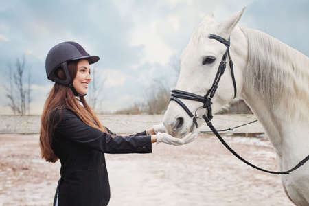 Happy jockey woman feeding white horse outdoors