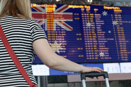 Woman looks at the scoreboard at the airport. Select a country Australia for travel or migration.