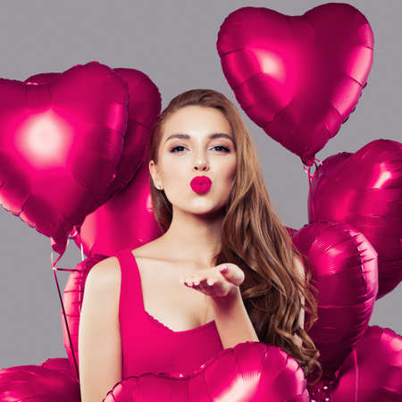 Glamorous woman with pink heart balloons portrait