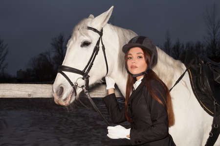 Portrait of stylish woman and white horse at night