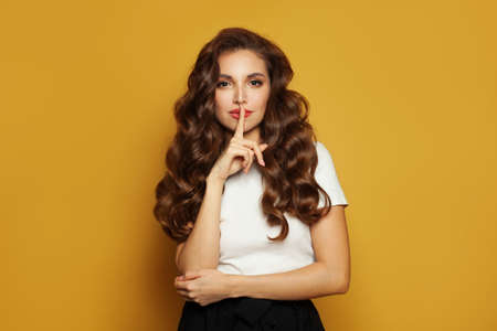 Beautiful young model woman keeps fore finger on lips, demonstrates silence gesture, ask to keep confidential information in secret on yellow background 版權商用圖片