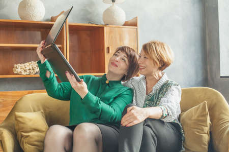 Two happy mature women choosing and buying online, e-commerce