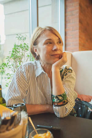 Mature woman with short ginger hair resting in cafe