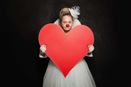 Happy woman clown showing red empty heart banner on black background Stockfoto