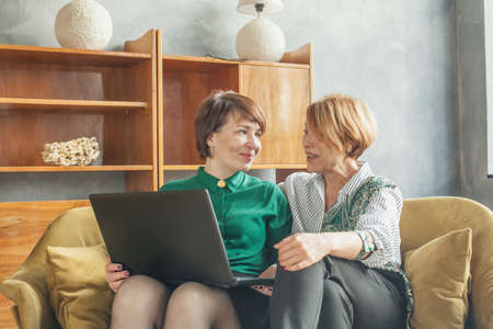 Happy mature women chatting and using laptop at home