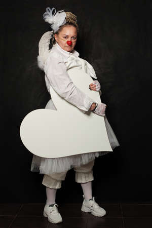 White clown woman with white empty heart banner on black background