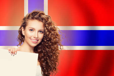 Cheerful woman showing white banner on the Norway flag background. Live, work, education and internship in Norway