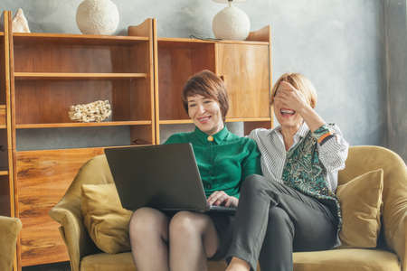 Senior mother and mature daughter having fun with laptop at home Banco de Imagens