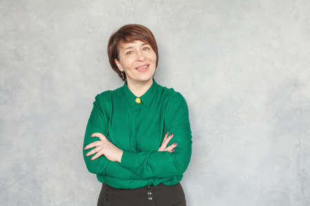 Happy smart business woman in green shirt on gray background, portrait Stock Photo