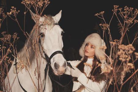 Junge hübsche Frau, die draußen mit Pferd spazieren geht Standard-Bild