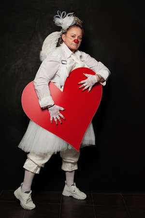 Portrait of actress lady in clown costume with red heart at work