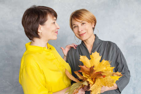 Autumn portrait of two mature women with fall maple leaves