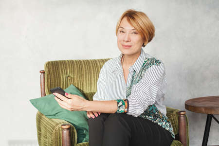 Happy mature woman used cell phone at home