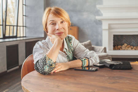 Perfect older woman with short ginger hair at home Stock Photo