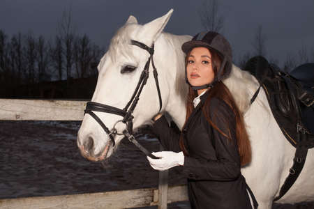 Portrait of beautiful woman with white horse outdoors, evening walk