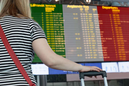 Woman looks at the scoreboard at the airport. Select a country Italy for travel or migration.