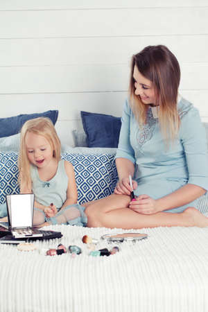 Happy mother and her daughter having fun with makeup cosmetics. Beautiful woman and her cute little girl  playing and smiling at home 写真素材