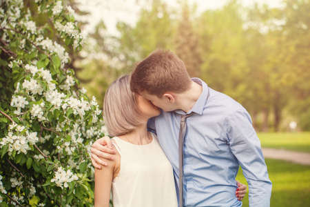 Kissing couple, young man and woman outdoor in spring sunny park 版權商用圖片