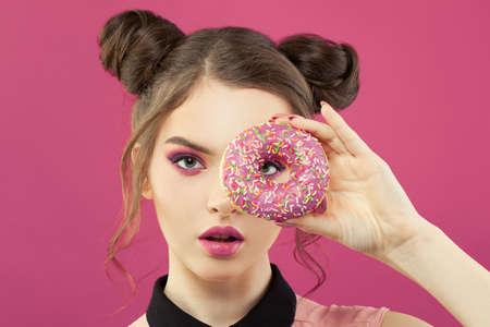 Mode portrait de jolie femme tenant un beignet sur fond rose vif