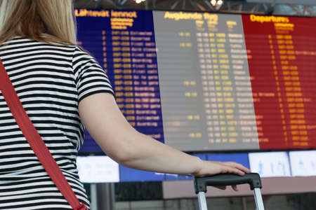 Woman looks at the scoreboard at the airport. Select a country France for travel or migration.