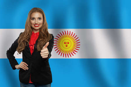 Happy woman on the Argentina flag background. Travel and learn spanish language Stock Photo