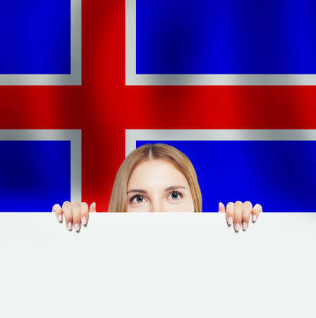 Iceland concept. Happy woman with white banner and the Icelandic flag background. Travel and learn Icelandic language