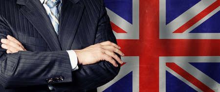 Businessman in a suit with his hands arms crossed on flag background