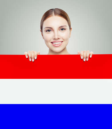 Love Netherlands! Happy woman smiling and showing on netherlandish flag background