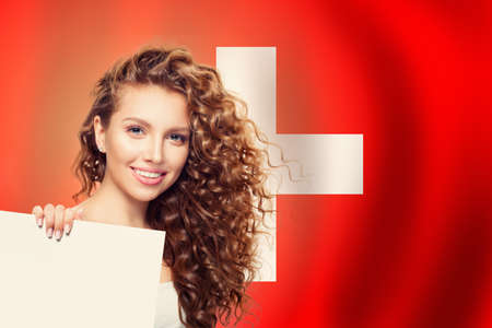 Love Switzerland concept. Happy beauty woman with white paper on swiss flag background