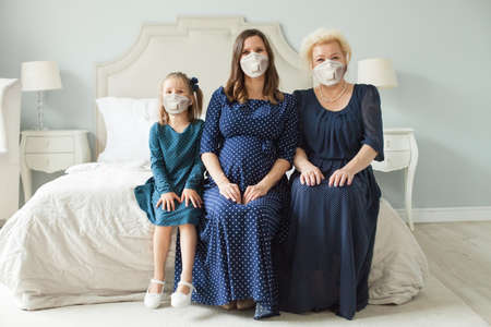 Happy familyin protective mask at home. Senior woman, pregnant adult woman and child girl. Mother, daughter, grandmother