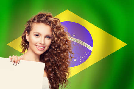 Happy cute girl with white banner against the Brazil flag background
