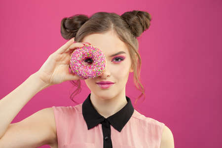 Cute fashion woman holding donut on vivid pink background 스톡 콘텐츠