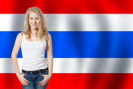 Travel and learn Thai language concept. Smiling blonde woman student against the Thailand flag background