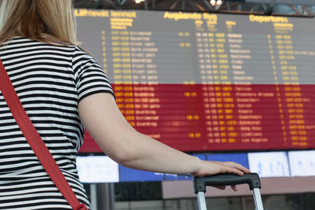 Woman looks at the scoreboard at the airport.