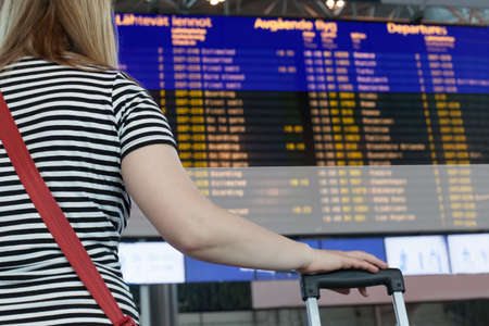Woman looks at the scoreboard at the airport. Select a country Estonia for travel or migration.
