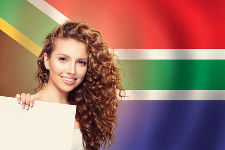 happy cute woman with white empty banner against the South Africa flag background