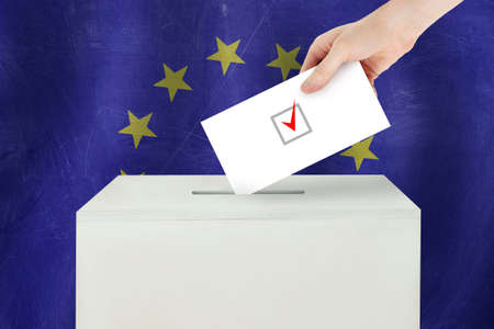 European Union Vote concept. Voter hand holding ballot paper for election vote on polling station
