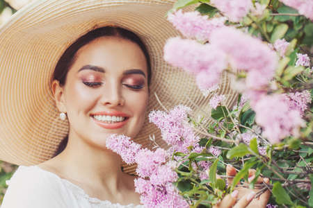 Elegant young woman in white hat with flowers outdoor